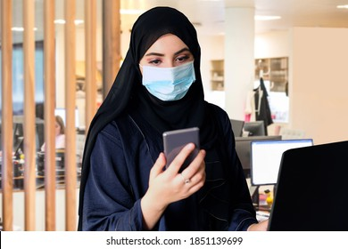 Middle East going back to work due to COVID19 pandemic wearing face mask and Arab Abaya Hijab while using smart phone.