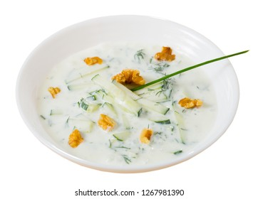 Middle East traditional summer dish Tarator, chilled vegetable soup with yogurt, cucumbers, greens, walnuts. Isolated over white background