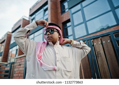 Middle Eastern arab business man posed on street against modern building with sunglasses.