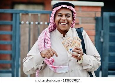 Middle Eastern arab business man posed on street against modern building with black handbag and euro moneys.