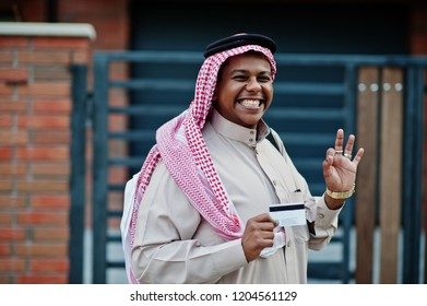 Middle Eastern arab business man posed on street against modern building with black handbag and credit card at hand.