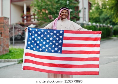 Middle Eastern arab man posed on street with USA flag. America and Arabian countries concept.