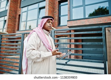 Middle Eastern arab man posed on street against modern building with tablet at hands.