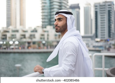 Middle Eastern Arab man standing alone at a terrace in Dubai Marina looking forward
