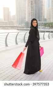 Middle Eastern Arab woman wearing traditional black abaya going with shopping bags