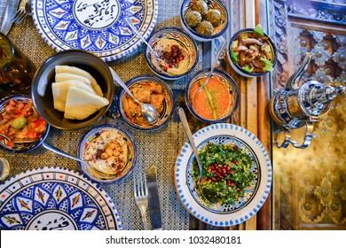 Middle eastern or arabic dishes and assorted meze, concrete rustic background. Meat kebab, falafel, baba ghanoush, muhammara, hummus, sambusak, rice, tahini, kibbeh, pita Halal food Lebanese cuisine