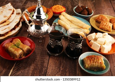 Middle eastern or arabic dishes and assorted meze, concrete rustic background. Turkish Dessert Baklava with pistachio. falafel with hommos.  Halal food. Lebanese cuisine. Tea pot
