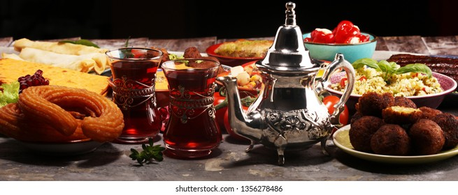 Middle eastern or arabic dishes and assorted meze, concrete rustic background. Falafel. Turkish Dessert Baklava with pistachio. Meat kebab, falafel, baba ghanoush, muhammara, hummus, tahini, kibbeh