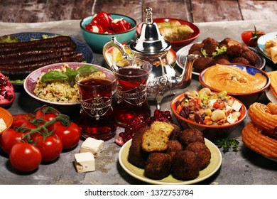 Middle eastern or arabic dishes and assorted meze, concrete rustic background. Falafel. Turkish Dessert Baklava with pistachio.