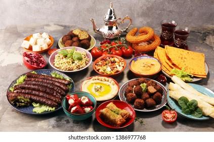 Middle eastern or arabic dishes and assorted meze, concrete rustic background. Falafel. Turkish Dessert Baklava with pistachio. Meat kebab, falafel, baba ghanoush, muhammara, hummus, tahini, kibbeh,