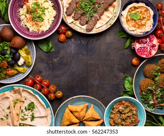 Middle eastern or arabic dishes and assorted meze on a dark background. Meat kebab, falafel, baba ghanoush, hummus, rice with vegetables, sambusak, kibbeh, pita. Halal food. Space for text. Top view