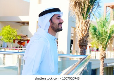 Middle Eastern Arabic guy side view smiling looking positive outlook wearing traditional kandora mens wear