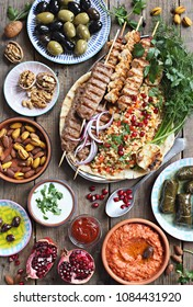 Middle eastern, arabic or mediterranean dinner table with grilled lamb kebab, chicken skewers  with roasted vegetables and appetizers variety serving on rustic outdoor table. Overhead view.