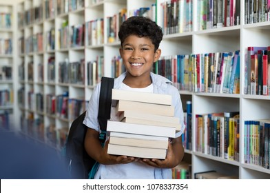 Middle eastern boy holding a stack of books against multi colored bookshelf in library.Portrait of happy arab schoolboy with backpack at school. Happy young indian child holding heap of books.