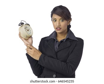 Middle eastern business woman standing holding a old fashion alarm clock; isolated on white background