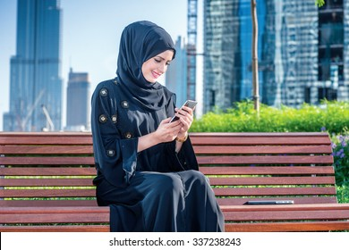 Middle Eastern businesswoman received message. Arab businesswomen in hijab holding of cell phone and read the message on the background of skyscrapers of Dubai. The woman is dressed in a black abaya