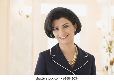 Middle Eastern businesswoman wearing pearl necklace