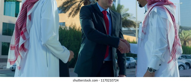 Middle eastern and caucasian businessmen shaking hands outdoor on a sunny day