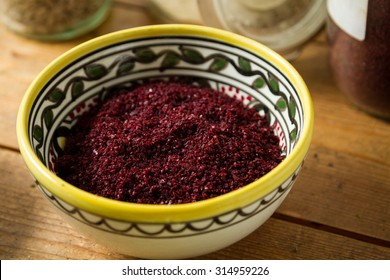 Middle Eastern cuisine: close-up on bowl of sumac. Sumac powder is used in Arabic cuisine to add zest and flavour to dishes. Jars of ginger and parsley and other herbs in the background.