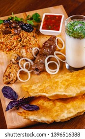 Middle eastern cuisine. Pasties, kebabs, pilaf, ayran on wooden cutting board. Close up