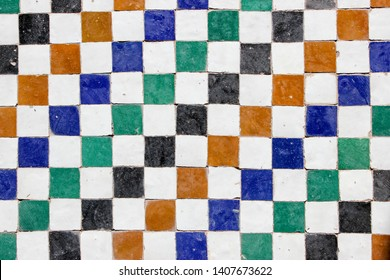 Middle eastern decorative tile pattern with white, orange, blue, green and black square tiles