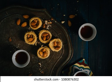 Middle Eastern dessert delicacy Knafeh served with Arabic black coffee. Top view of Turlish Baklava and coffee food photography.