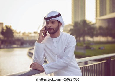 Middle Eastern Emirati Man in traditional clothing called kandura is standing on terrace in Dubai Marina and talking with his mobile.