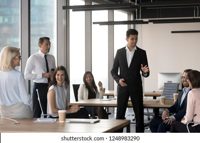 Middle eastern ethnicity team leader representing new project to colleagues standing in modern coworking area. Seven multiracial coworkers gathered at briefing for sharing business ideas, information