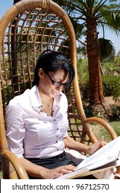 A middle eastern female with a book in the garden