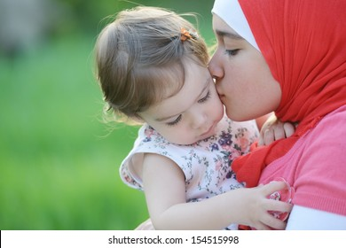 Middle eastern female with little baby playing in summer grass