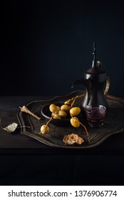 Middle Eastern food still life photography with Dallah and dates with rustic look. Raw dates, traditional arabic coffee pot and coffee cups placed on a antique tray.