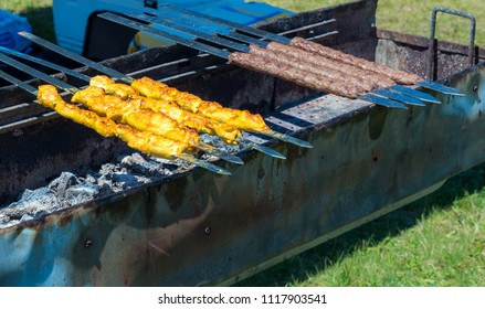 Middle eastern kabobs on a barbecue. There are both yellow chicken kabobs and brown beef kabobs. They are skewered with flat metal knives above a long metal BBQ.