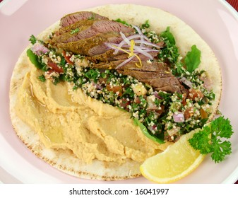 Middle Eastern lamb fillet on pita bread with hummus and tabouleh and lemon parsley.