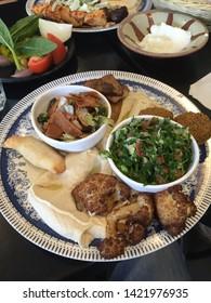 Middle eastern Lebanese Arabic food. Hommos, tabouli salad, fatosh, falafel and cauliflower. Vegetarian mixed plate.