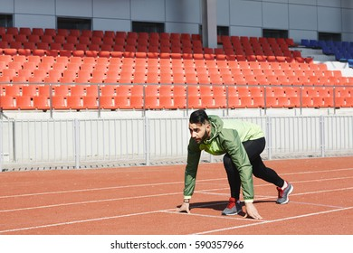 Middle Eastern male athlete ready to start running on stadiums sprint track