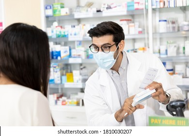 Middle eastern male pharmacist wearing protective hygienic mask to prevent infection selling medications to woman patient to prescription and making drug recommendations in modern pharmacy