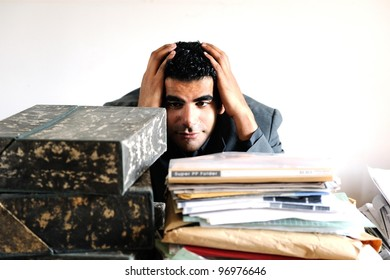 A middle eastern male with piles of papers and files
