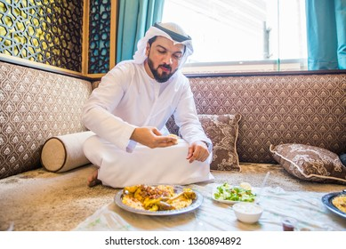 Middle eastern man wearing kandora eating in a cafè restarant in Dubai