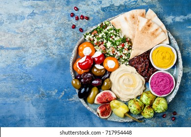 Middle Eastern meze platter with green falafel, pita, sun dried tomatoes, pumpkin and beet hummus.Mediterranean appetizer party idea