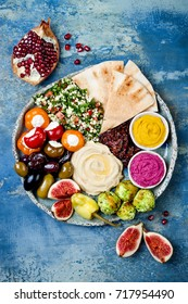 Middle Eastern meze platter with green falafel pita, sun dried tomatoes, pumpkin and beet hummus, olives, stuffed peppers, tabbouleh, figs. Mediterranean appetizer party idea