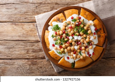 Middle Eastern pita with chickpeas, yogurt and pomegranate seeds close-up on a plate on the table. horizontal top view from above