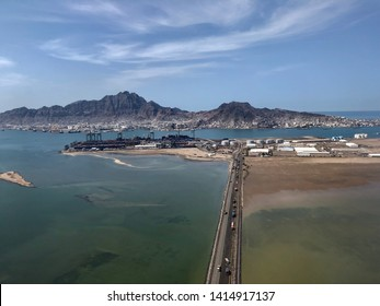 Middle eastern port city of Aden, beautiful mountain, blue sky and blue waters. Road with cargo trucks being loaded for much needed relief for Yemen