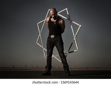 Middle Eastern rock style man practicing with a star shaped fire artist prop.