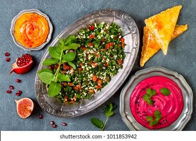 Middle Eastern traditional dinner. Authentic arab cuisine. Tabbouleh, sambusek, pumpkin and beet hummus. Top view, flat lay, overhead