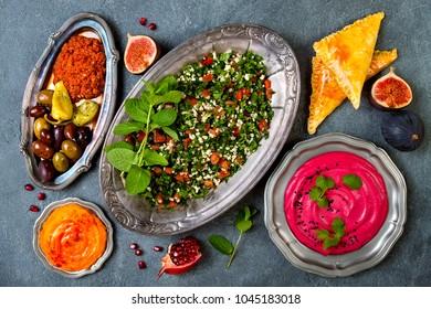 Middle Eastern traditional dinner. Authentic arab cuisine. Tabbouleh, sambusek, muhammara, pumpkin and beet hummus. Top view, flat lay, overhead