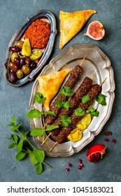 Middle Eastern traditional dinner. Authentic arab cuisine. Meze party food. Lamb kebab, sambusek, muhammara.Top view, flat lay, overhead