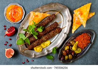 Middle Eastern traditional dinner. Authentic arab cuisine. Lamb kebab, sambusek, muhammara, pumpkin hummus. Top view, flat lay, overhead