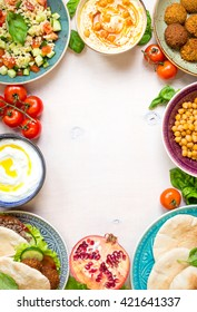 Middle eastern traditional dishes on a white background. Doner kebap, vegetarian pita, bowl with hummus, falafel, tabbouleh bulgur salad, boiled chickpea, olive oil dip, pomegranate. Space for text