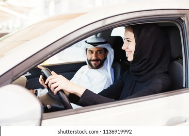 Middle eastern woman in hijab driving a car with her husband