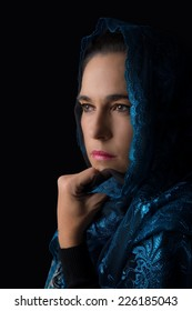 Middle Eastern woman portrait looking sad with a blue hijab artistic conversion